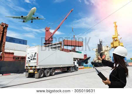 The Women Engineer Working With Container Cargo Freight Ship In Shipyard At Dusk For Logistic Import