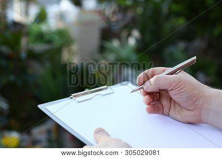 Human Hand Writing On Clipboard With White Paper. Man Holding Pen And Blank Document Close-up Photog