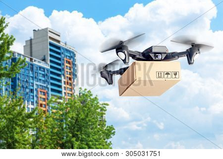 Drone With Cardboard Box Makes Delivery By Air. Drone With Camera Carries Postal Parcel. Background