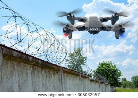 Police Drone Patrols The Area Across The Sky. Guarding The Wall With Barbed Wire Drone With Blue And
