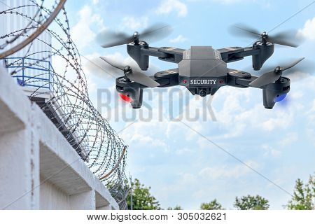 Security Drone Patrols The Territory Across The Sky. Guarding The Wall With Barbed Wire Drone With B