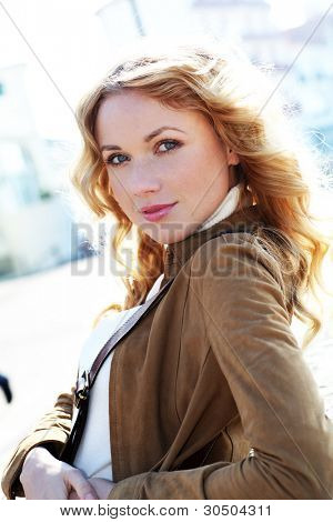 Beautiful blond woman in town by sunny day