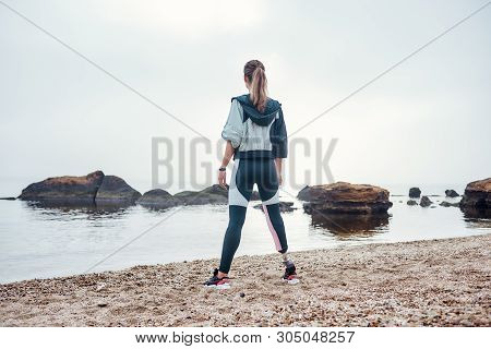 I Adore Living By The Sea. Back View Of Confident Disabled Sporty Woman In Sportswear With Prostheti