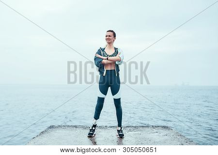 Feeling Happy. Positive And Motivated Disabled Woman In Sports Clothing With Prosthetic Leg Standing