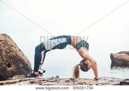 Flexible Body. Young Disabled Athlete Woman In Sportswear With Prosthetic Leg Making A Gymnastic Exe