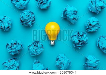 poster of new idea concept with blue crumpled office paper and light bulb. top view of business idea concept over blue background. creative idea during brainstorming session concept. great idea during creative process concept