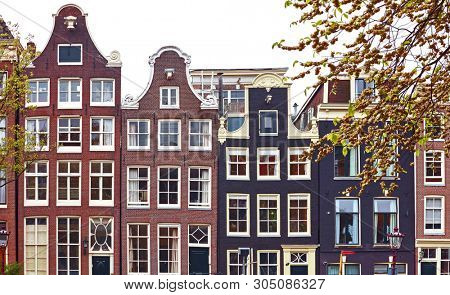 Amsterdam Netherlands dancing houses with traditional deutch windows. Landmark in old european city. Architectural details and roofs.