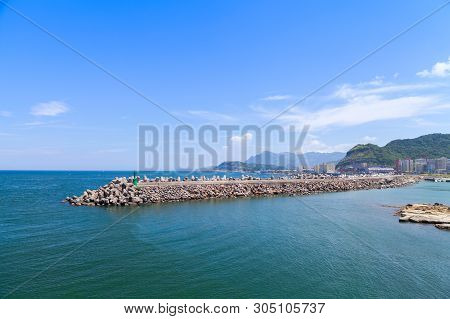 Breakwater Structure Made Of Concrete Blocks Under Blue Cloudy Sky. Keelung City, Taiwan