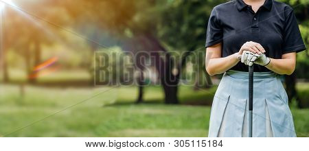 Close Up Portrait Of Young Female Golf Player Wearing Sportswear Swinging On Green Field.young Woman