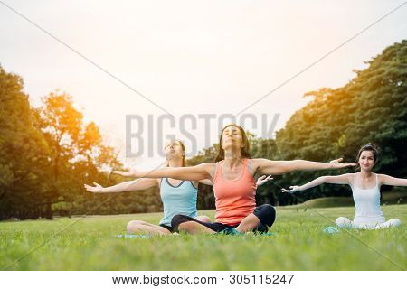Yoga Woman On Green Grass.group Of Adults Attending A Yoga Class Outside In Park.family Or Friends E
