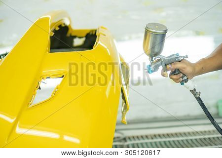 Man With Protective Clothes And Mask Painting Car Using Spray Compressor ,yellow Front Bumper
