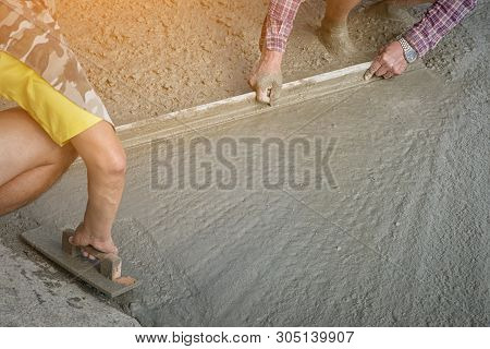 Workers Person Not Wearing Dirt Boots Digging With Hoe (shovel) On Concrete Floor, Construction Work