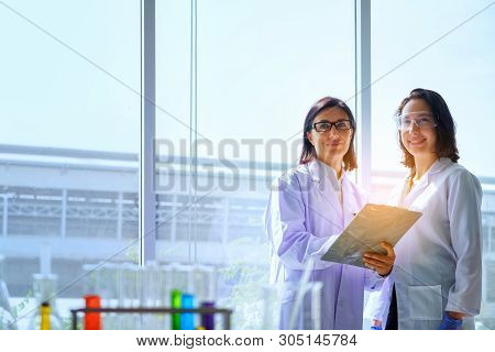 Young Female Scientist Standing With Techer In Lab Worker Making Medical Research In Modern Laborato