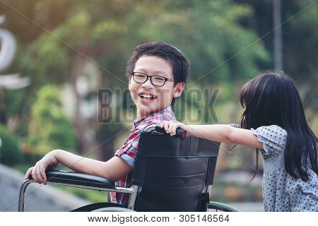 Happy Boy In Wheelchair With Girl Try Drive A Wheelchair Of Her Brother Smile, Family Time