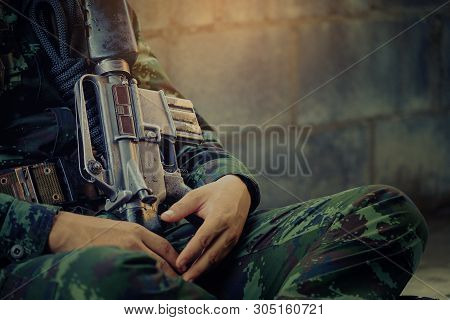 Hunting, War, Army And People Concept - Young Soldier, Ranger Or Hunter With Gun Sitting And Sleepin