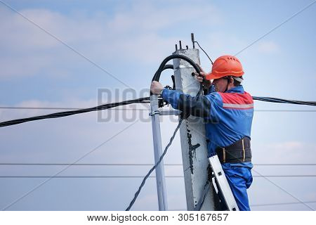 Electrical Engineer Performs Wiring On A High Pole Standing On The Stairs. High-rise Electrical Work