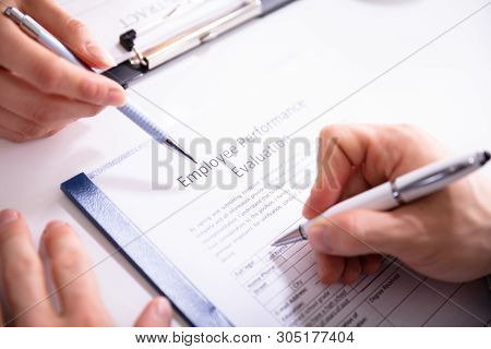 Close-up Of A Person Filling Performance Evaluation Form Of Employee Over Desk
