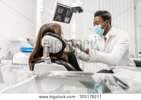 Doctor Treats Teeth. Young African Male Dentist With A Patient. Woman In The Dentist Chair At Dental