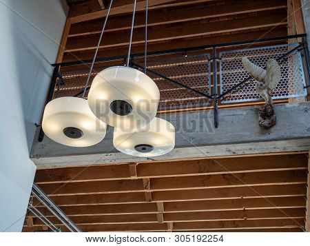 Hanging light fixture with fixed owl near second story of an open beam building poster