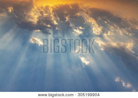 Besutiful Ray Of Sunlight Breaking Through Clouds At Sunset.