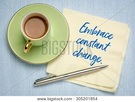 Embrace constant change - handwriting on a napkin with a cup of coffe