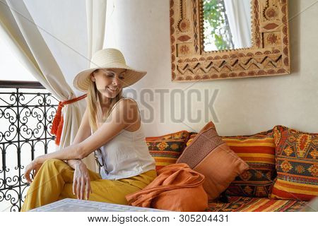Elegant woman sitting in traditional moroccan riad poster