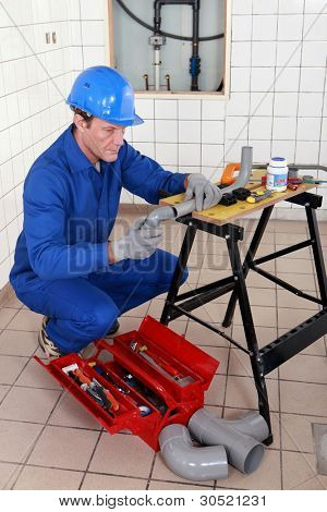 Plumber adjusting pipe