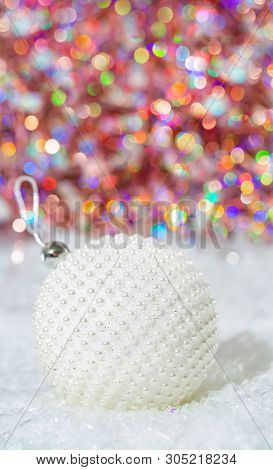 Holiday Decoration.white Ball With Nacre Pearls On A Snow And Beautiful Blurred Colorful Background