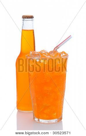 A cold glass of orange soda filled with ice and a drinking straw, with a bottle tucked in behind.  Vertical format with a white background with reflection.