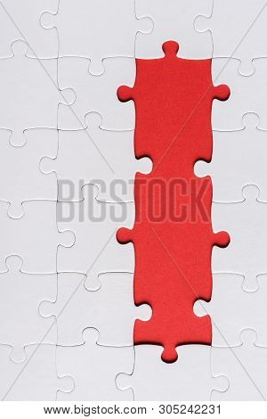 top view of white connected ans incomplete jigsaw puzzle pieces isolated on red poster
