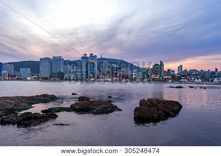 Busan, South Korea - April 2019: Cityscape With Illuminated Lights On Buildings During Sunset Along
