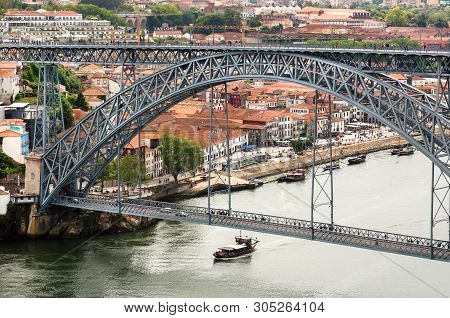 Porto, Portugal: Riverboat Sailing On The River Douro, With Double-deck Metal Arch Bridge On 19 May,