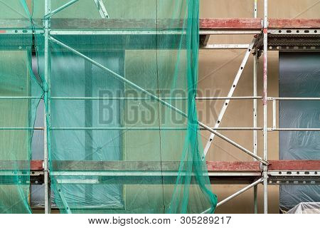 Building Facade Renovation, Old House Reconstruction, Repair. Scaffold In Front Of Building Facade C