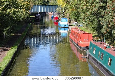 Barges moored to the bank on the Grand Union Canal at Lapworth in Warwickshire, England poster