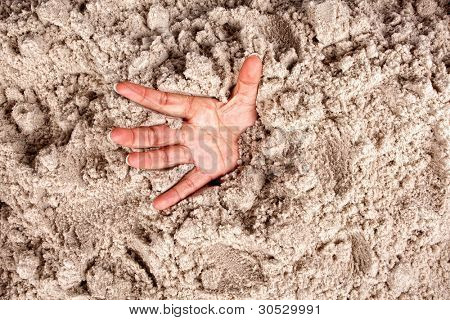 Hand on a beach sinking or drowning in quicksand