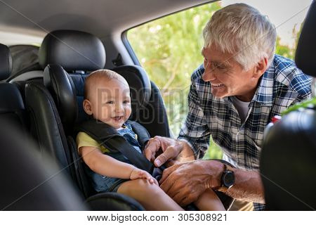 poster of Grandfather tying baby in child seat. Cute little boy going for road trip with grandfather. Happy senior man and happpy smiling grandchild enjoying car trip. Toddler boy buckled into car seat.