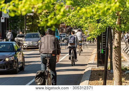 Montreal, Canada - 6 June 2019: People Are Riding Bikes On A Cycle Path, On Laurier Street In The Pl