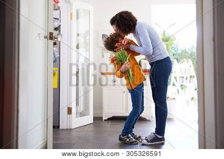 Loving Son Giving Mother Bunch Of Flowers To Celebrate Mothers Day At Home