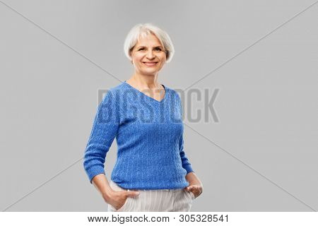 old people concept - portrait of smiling senior woman in blue sweater over grey background