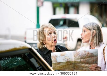 Two Women Lost In A City Center Checking Road Map