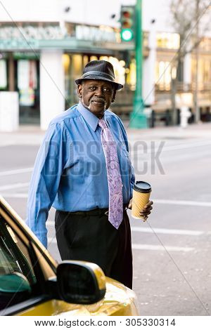 Handsome Senior Man Downtown With Takeout Coffee
