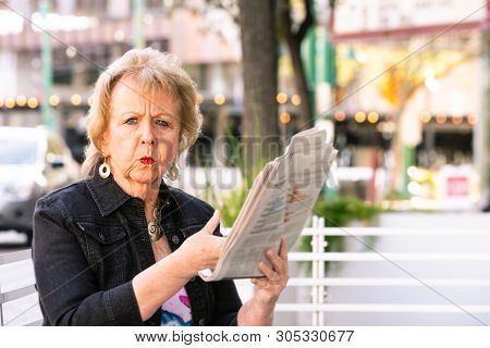 Upset Woman Downtown With Newspaper Reacting To Story