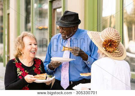 Three Seniors Downtown With Slices Of Pizza