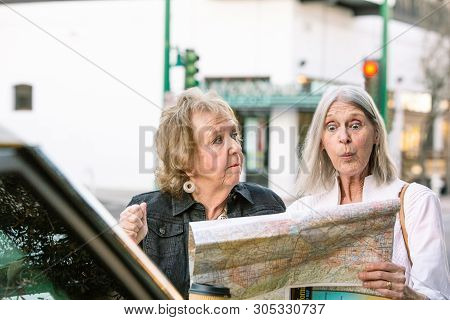 Two Confused Women In A City Center Checking Road Map
