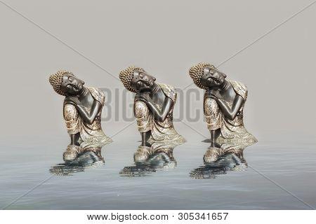 Budha Meditating In Reflection In Black Background