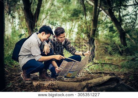 Tourists With Backpack To The Forest Looking At Map To Learn Hiking Trails.
