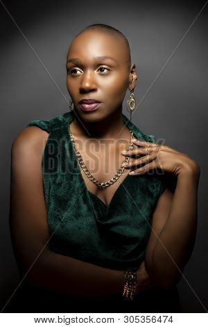 Black African American Female Fashion Model With A Bald Hairstyle In A Studio.  The Portrait Shows T