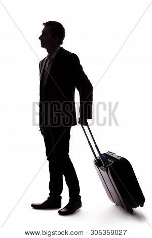 Silhouette Of A Businessman Going On A Business Trip And Traveling With Luggage.  The Man Is Carryin