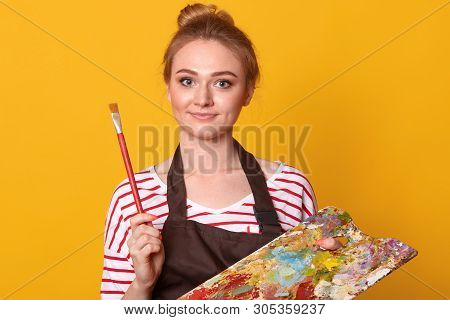 Studio Shot Of Young Beautiful Woman Wearing Wite Casual Shirt With Red Stripes And Brown Apron On Y