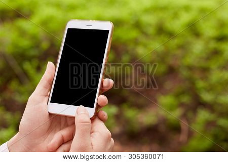 Hands Of Unknown Holding Modern Device Being Around Nature, Black Screen, Turning Off Smartphone, No